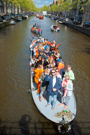 revellers: AMSTERDAM NETHERLANDS APRIL 27: People on Party Boat with unlimited beer soda and wine aboard on King Day on April 27 2015. King Day is the largest openair festivity in Amsterdam.