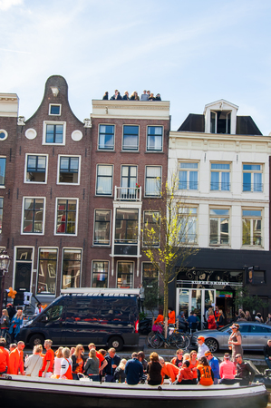 revellers: AMSTERDAM-APRIL 27: Locals and tourists celebrate Kings Day along the Singel canal on April 27,2015 in Amsterdam, the Netherlands. Group of people watch the festival from the roof. Editorial