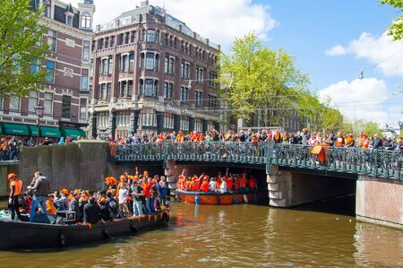 revellers: AMSTERDAM-APRIL 27: Kings Day Koningsdag boating on the Singel canal, crowd of people watch the festival on the bridge on April 27, 2015. Kings Day is held on 27 April every year. Editorial
