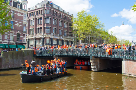 revellers: AMSTERDAM-APRIL 27:  Kings Day also known Koningsdag on the Singel canal,  people watch the festival on the bridge on April 27, 2015. Kings Day is held on 27 April every year. Editorial