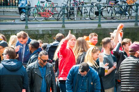 revellers: AMSTERDAM-APRIL 27: Kings Day boating, locals have fun on the boats on April 27, 2015 in Amsterdam, the Netherlands.