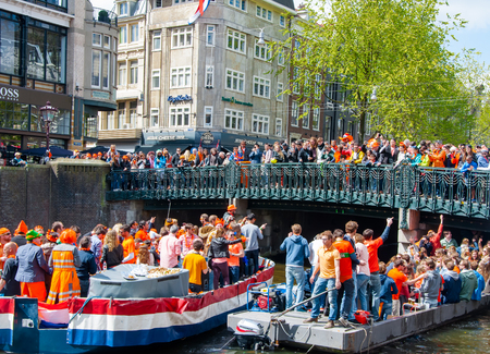 revellers: AMSTERDAM, NETHERLANDS-APRIL 27: Party Boat with crowd of people on the bridge on Kings Day on April 27,2015. Kings Day is the largest open-air festivity in Amsterdam.