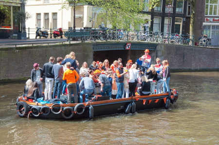 revellers: AMSTERDAMAPRIL 27: King Day boating on April 27 2015 in Amsterdam the Netherlands. King Day is held on 27 April the king birthday every year. Editorial