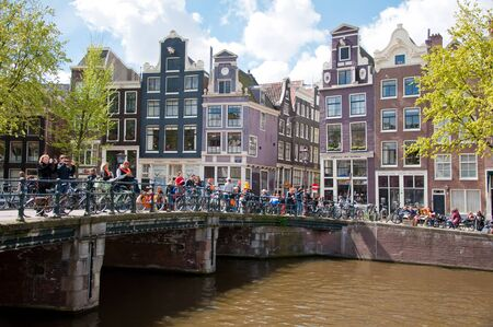revellers: AMSTERDAM APRIL 27: King Day boating through Amsterdam canals people have fun on the bridge on April 27 2015. King Day Koningsdag is held on 27 April the king birthday every year. Editorial