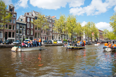 revellers: AMSTERDAMNETHERLANDSAPRIL 27: Amsterdam canal full of boats during King39s Day on April 27 2015 the Netherlands. Kings Day is biggest festival celebrating the birth of Dutch royalty. Editorial