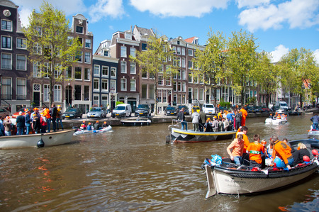 revellers: AMSTERDAM NETHERLANDS APRIL 27: Amsterdam canal full of boats during King Day on April 27 2015 the Netherlands. King Day is the largest openair festivity in Amsterdam the Netherlands. Editorial