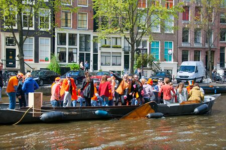 revellers: AMSTERDAM APRIL 27: King Day boating locals have fun on the boats on April 27 2015 in Amsterdam the Netherlands. King Day Koningsdag is held on 27 April every year.