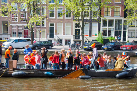 revellers: AMSTERDAM APRIL 27: King Day boating people have fun on the boats on April 27 2015 in Amsterdam the Netherlands. King Day Koningsdag is held on 27 April the king birthday every year. Editorial