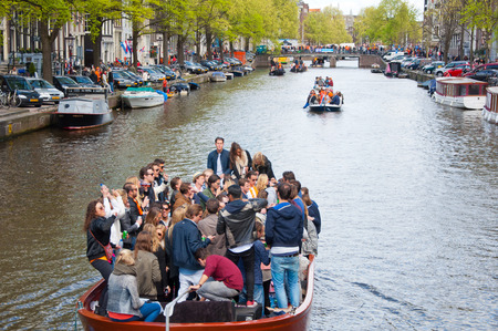 revellers: AMSTERDAM APRIL 27: King Day boating through canals on April 27 2015 in Amsterdam the Netherlands. King Day Koningsdag is held on 27 April the king birthday every year.
