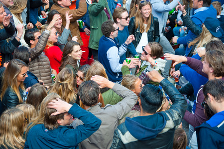 revellers: AMSTERDAM APRIL 27: Openair party people dance during King Day on April 27 2015 in Amsterdam the Netherlands. Kings Day is the biggest festival celebrating the birth of Dutch royalty.
