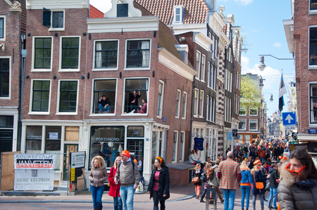 revellers: AMSTERDAM APRIL 27: Crowd of people in orange celebrate King Day around Amsterdam street on April 272015. King Day Koningsdag is held on 27 April the king birthday every year. Editorial
