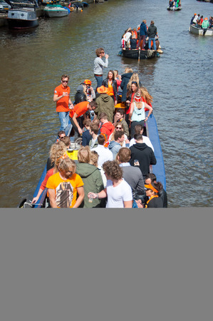 revellers: AMSTERDAM APRIL 27: Local people on Party Boat with unlimited beer celebrate King Day on April 27 2015. King Day is the largest openair festivity in Amsterdam.