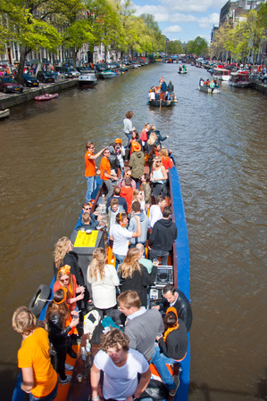 revellers: AMSTERDAM APRIL 27: Local people on Party Boat with unlimited beer soda and wine aboard celebrate King Day on April 27 2015. King Day is the largest openair festivity in Amsterdam. Editorial