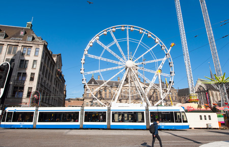 dam square: AMSTERDAM-APRIL 27: Big wheel on Dam Square on the eve of Kings Day, Madam Tussauds museum on the left-hand side on April 27,2015.  Kings Day is the largest open-air festivity in Amsterdam. Editorial
