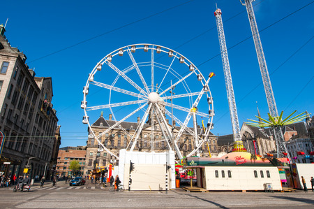 dam square: AMSTERDAM,NETHERLANDS-APRIL 27: Ferris wheel on Dam Square on the eve of Kings Day on April 27,2015 in Amsterdam.  Kings Day is the largest open-air festivity in Amsterdam. Editorial