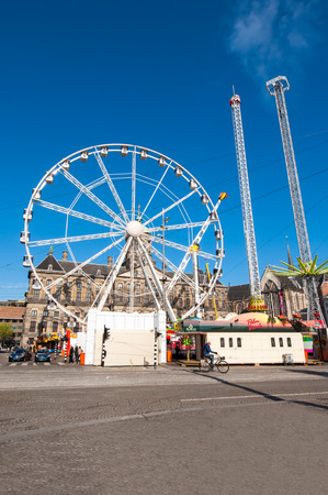 dam square: AMSTERDAM,NETHERLANDS-APRIL 27: Attractions on Dam Square on the eve of Kings Day on April 27,2015 in Amsterdam.  Kings Day is the largest open-air festivity in Amsterdam.