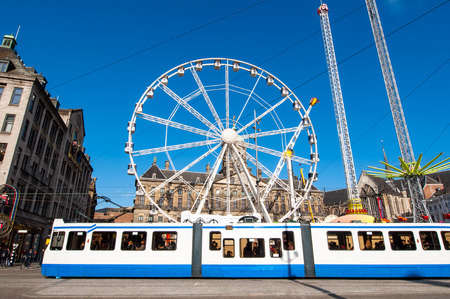 dam square: AMSTERDAM,NETHERLANDS-APRIL 27: Ferris wheel with Royal Palace in the background on Dam Square on the eve of Kings Day on April 27,2015.  Kings Day is the largest open-air festivity in Amsterdam. Editorial