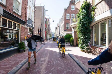 neighbourhood: AMSTERDAM-APRIL 30: Jordaan neighbourhood, tourists ride bicycles on April 30,2015. The Jordaan is a neighbourhood of the city of Amsterdam with its famous art galleries, particularly for modern art.