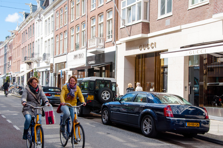 chanel: AMSTERDAM-APRIL 30: The P.C.Hooftstraat fashion street with the world biggest brands, people ride a bike on April 30 ,2015. P.C.Hooftstraat  is a small street next to the Rijksmuseum.
