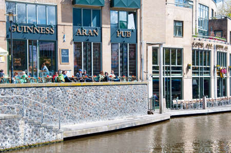 revellers: AMSTERDAM-APRIL 30: Undefined tourists have breakfast in Aran Irish Pub on April 30,2015, the Netherlands.  Aran Irish Pub is a very relaxing and enjoyable place. Editorial