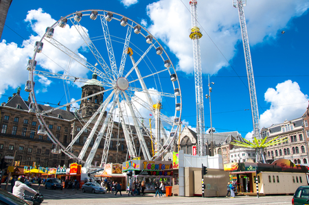 big wheel: AMSTERDAM-APRIL 30: Dam Square with big wheel and Royal Palace on the background on April 30, 2015 in Amsterdam, Netherlands.