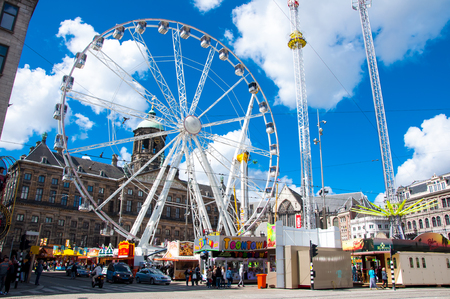 dam square: AMSTERDAM-APRIL 30: Dam Square with Ferris wheel and Royal Palace on the background on April 30, 2015 in Amsterdam, Netherlands. Editorial