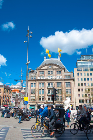 dam square: AMSTERDAM-APRIL 30: Undefined people cross the street on bikes on Dam Square, De Bijenkorf flagship store is visible on the background on April 30, 2015 in Amsterdam, Netherlands. Editorial