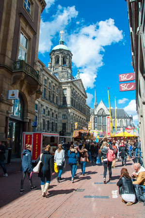 dam square: AMSTERDAM-APRIL 30: Crowd of people go shopping in Kalverstraat street, Dam Square is visible in the background on April 30,2015. The Kalverstraat is a busy shopping street of Amsterdam. Editorial