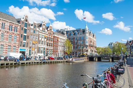 revellers: Amsterdam-April 30: Rokin canal with bikes parked along the bank, Hotel de lEurope is visible on the left, tourists enjoy cityscape on the opposite side on April 30, 2015, the Netherlands.