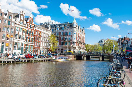 revellers: Amsterdam-April 30: Rokin canal with bikes parked along the bank, famous Hotel de lEurope is visible in the background, people enjoy cityscape on April 30, 2015, the Netherlands. Editorial