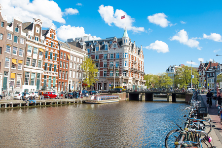 revellers: Amsterdam-April 30: Rokin canal with bikes parked along the bank, Hotel de lEurope is visible in the background, tourists enjoy cityscape on the opposite side on April 30, 2015, the Netherlands. Editorial