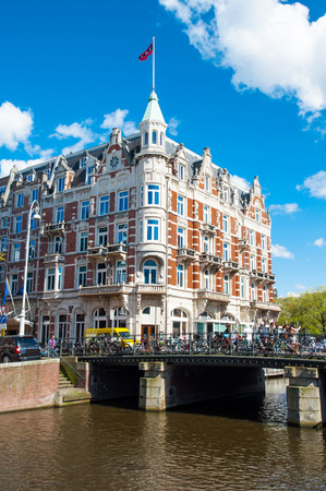 revellers: Amsterdam-April 30: Rokin canal with famous Hotel de lEurope, people cross the bridge on April 30,2015, the Netherlands.