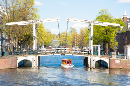 amstel river: Amsterdam-April 30: Magere Brug (Skinny Bridge) as seen from the water on April 30, 2015. Bridge provides a nice spot to take in sweeping views of the Amstel river with the Carre Theatre close by.