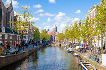 red light district: Amsterdam-April 30: Amsterdams Red Light District, crowd of tourists go sightseeing, the Church of St. Nicholas is visible in the distance on April 30,2015, the Netherlands.