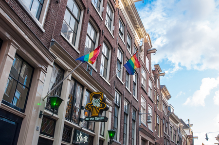 opalescent: Amsterdam-April 30: Rainbow flags on the medival building in red light district on April 30,2015, the Netherlands.