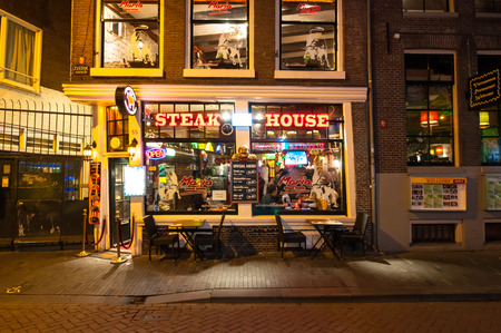 street drug: Amsterdam-May 01: Row of local steakhouses and restaurants at night in red-light district on May 01,2015 in Amsterdam, the Netherlands.