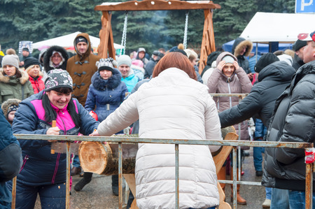 kokoshnik: RUSSIA, BRYANSK-MARCH 13: Undefined people take part in contest saw up the log on Maslenitsa day on March 13,2016 in Bryansk city. Maslenitsa is a week-long festival before Great Fast.
