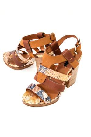 Pair of womens open-toe sandals decorated snake  leather on white. Stock Photo