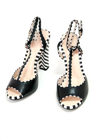Pair of female high heeled slingbacks with striped heels.