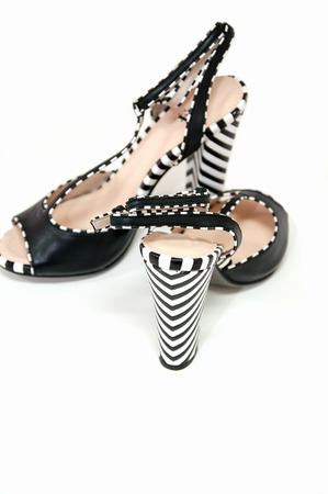 Pair of female high heeled slingbacks with striped heels isolated on white. Stock Photo