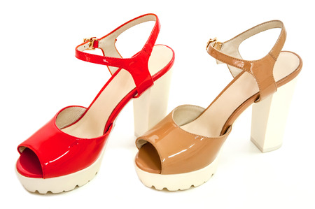Pair of red and beige womens high heeled patent shoes on white background. Stock Photo