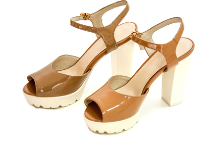 Pair of beige womens high heeled shoes from patent leather on white background.