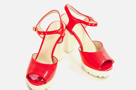 Pair of red womens high heeled patent shoes on white.