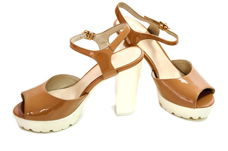 Pair of beige womens high heeled shoes on white background. Stock Photo