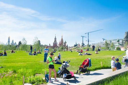 Moscow, Russia May-27,2018: Zaryadye Park crowd of people enjoy sunny day in the park, Moscow Kremlin in the background.