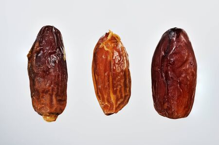 Raw dried organic dates ready to eat on white background