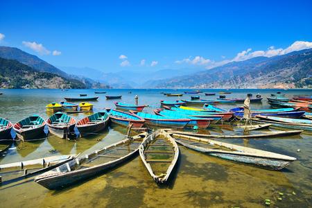 phewa: Colorful boats on Phewa lake, Pokhara, Nepal. Wide angle landscape Stock Photo