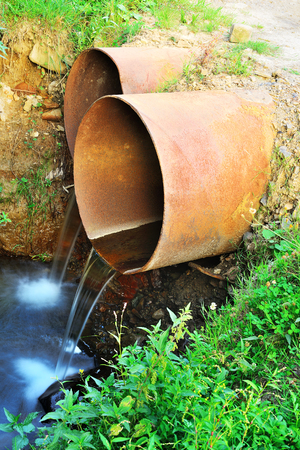 Water running from rusty sewers, environment concept. Stock Photo