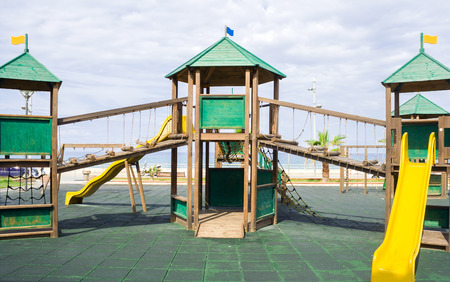 Green wooden games structure in urban area next to the sea photo