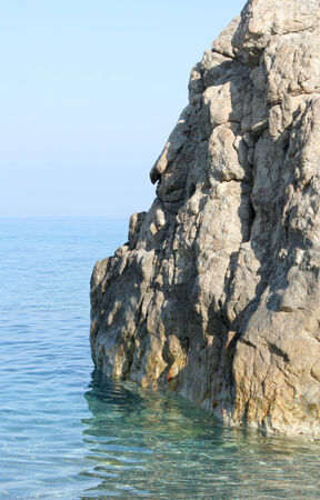 Rock overhanging in the pure blue sea photo